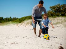 Father And Son Run After The Ball Royalty Free Stock Photos