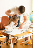 Father angry at daughter doing homework Stock Image