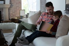 Father ans son reading book in living room. At home stock photo