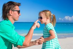 Father apply sunblock cream on his little child nose Stock Photos