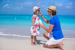 Father apply sunblock cream on his little daughter Stock Photos