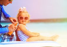 Father applying sunblock cream on daughters. Shoulder, sun protection Royalty Free Stock Images
