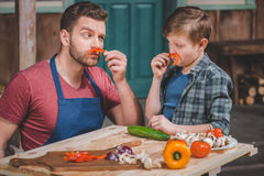 Father in apron and cute little son having fun with pepper moustaches Royalty Free Stock Photos
