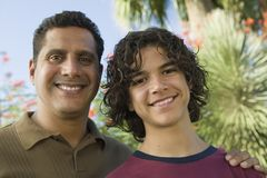 Father with Arm Around Son (13-15) front view portrait. stock images