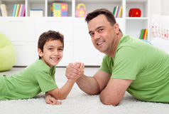 Father arm wrestling with his boy Stock Photography