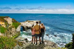 Father with arms around his family looking at beautiful ocean view. People on hiking trip in the mountains. Santa Cruz, California, USA royalty free stock image