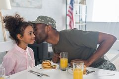 Father army uniform kissing african american daughter. By kitchen table royalty free stock photography