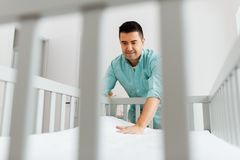 Father arranging baby bed with mattress at home royalty free stock images