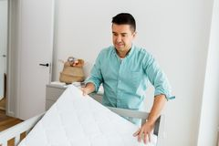 Father arranging baby bed with mattress at home stock image
