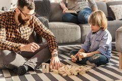 Father arranging bricks with son. Father arranging wooden bricks with his son while sitting on carpet stock images