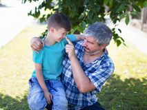 Father as lie detector. Pushing sons nose, outdoors Stock Images