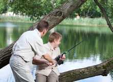 Father asks a fishing tackle from son too to fish. The father asks a fishing tackle from the son too to fish Royalty Free Stock Photos