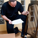 Father assembles new cot. A father assembles a new baby bed (cot, crib Royalty Free Stock Image