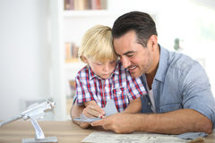 Father assembling toy with his son. Father and kid making a plane model Royalty Free Stock Image