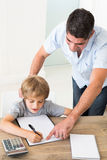 Father assisting boy in solving maths Royalty Free Stock Photo