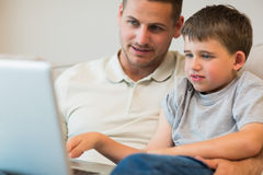 Father assisting boy in using laptop Stock Images