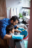 Father assisting son for cleaning utensils at home. High angle view of father assisting son for cleaning utensils at home Royalty Free Stock Photos