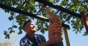 Father assisting son on climbing monkey bars at playground 4k