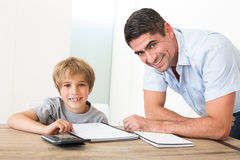 Father assisting son with homework Royalty Free Stock Photos