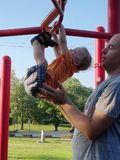 Father assisting son playing on monkeybars. A toddler boy and his father playing outside on monkey bars at a park with playground equipment on a gorgeous spring stock photography