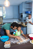 Father assisting son for rolling dough. With men using tablet in background Royalty Free Stock Image