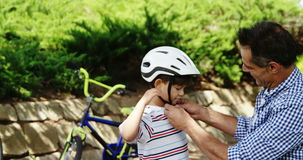 Father assisting son in wearing bicycle helmet in park stock video footage