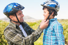 Father attaching his son cycling helmet Royalty Free Stock Photo
