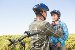 Father attaching his son cycling helmet Royalty Free Stock Image