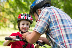 Father attaching his sons cycling helmet Stock Image