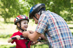 Father attaching his sons cycling helmet Royalty Free Stock Image