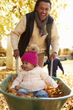 Father In Autumn Garden Gives Daughter Ride In Wheelbarrow Stock Photo