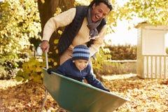 Father In Autumn Garden Gives Son Ride In Wheelbarrow stock photography