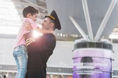 Father aviator rising up child. Family reunification. Cheerful pilot is holding little son and looking at him with sincere smile. Profile. Copy space on right Royalty Free Stock Photo