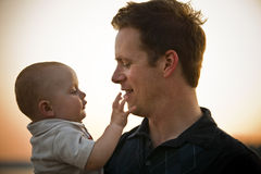 Father and Baby. At sunset, with baby touching father's chin. Horizontal Royalty Free Stock Photo