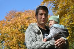 Father and baby on the Autumnal background royalty free stock photo