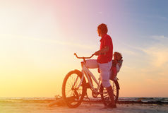 Father and baby biking at sunset Royalty Free Stock Photos