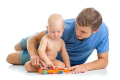 Father and baby boy have fun with musical toys Royalty Free Stock Images