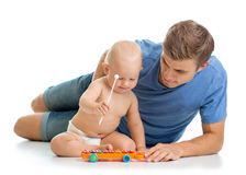 Father and baby boy have fun with musical toys. Isolated on wh Stock Images