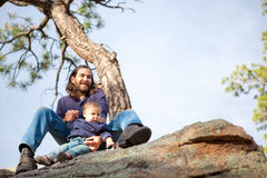 Father and baby boy in nature. Under a pine tree on cliffs, shallow DOF, child in focus Royalty Free Stock Photography