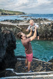 Father and baby boy play near the ocean shore in Garachico Royalty Free Stock Images