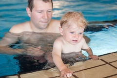 Father and baby boy swimming in a swimming pool Stock Photo