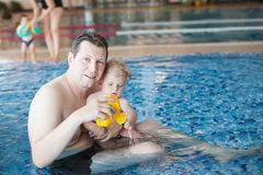 Father and baby boy swimming in a swimming pool Stock Photography