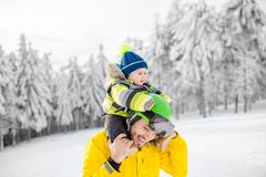 Father with baby boy during the winter vacations. Portrait of a happy father with baby boy standing in winter spots clothes outdoors during the winter vacations stock photos