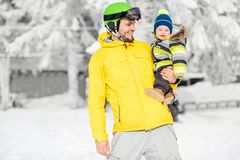 Father with baby boy during the winter vacations. Portrait of a happy father with baby boy standing in winter spots clothes outdoors during the winter vacations stock images