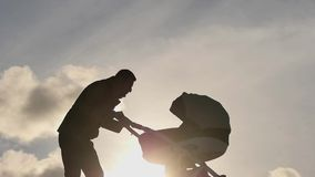 Father with baby carriage entertain and care of the child silhouette. Man with baby carriage entertain and care of the child silhouette stock video