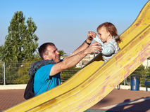 Father and baby child little boy playing on slide Stock Image