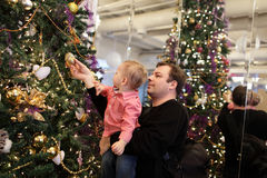 Father with baby by Christmas tree Royalty Free Stock Photo