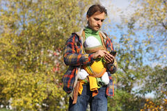 Father with baby in colorful sling dials number on mobile phone. On the background of autumn trees Royalty Free Stock Image
