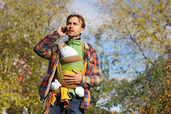 Father with baby in colorful sling talking on a mobile phone Royalty Free Stock Photos