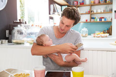 Father With Baby Daughter Checking Mobile Phone In Kitchen Stock Photography